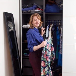 Anjolieke voor haar kledingkast met een jurk in haar hand