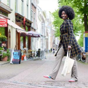 Michelle in een winkelstraat met een boodschappentas