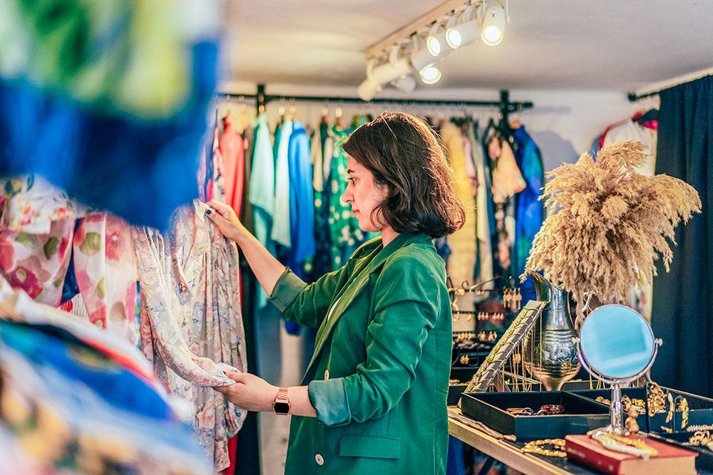 Vrouw bekijkt kleding in rek
